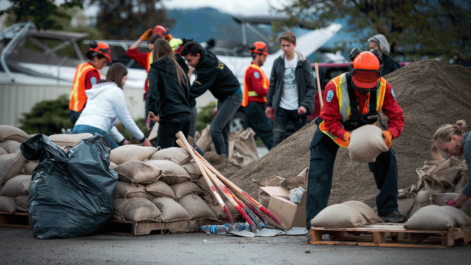 Group of workers creating sandbag wall against flood waters