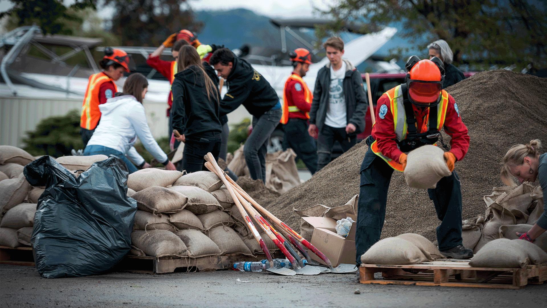 Group of workers creating sandbag wall against flood waters