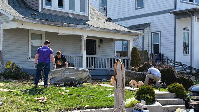 Nashville, Tennessee, 2020: People clean trash from their yard and start to cut a fallen tree the morning after a tornado rips through Nashville.